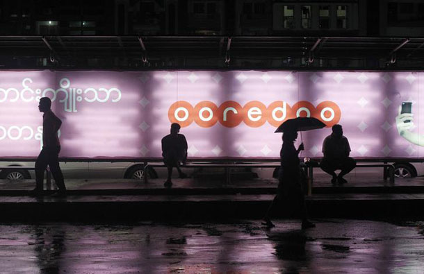 People sit at a bus station in front of an Ooredoo advertisement as they wait for a bus in Rangoon, August 1, 2014. (Photo: Soe Zeya Tun / Reuters)