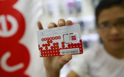 A woman shows a sim card from Qatar's Ooredoo after buying it from a phone shop in Rangoon, July 31, 2014. (Photo: Reuters)