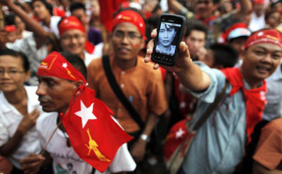A man shows a phone with a picture of Aung San Suu Kyi as election results are revealed on the screen in front of the head office of the National League for Democracy in Rangoon, April 1, 2012. (Photo: Damir Sagolj / Reuters)