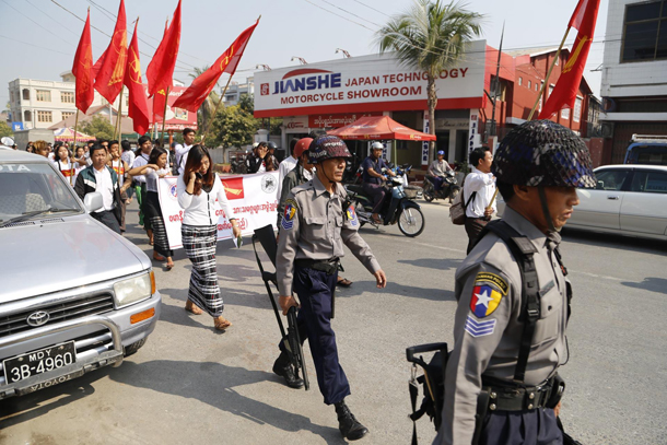 Police accompany student activists on a protest march to Mandalay University on Wednesday, the one-year anniversary of the start of a protest that ended violently several weeks later. (Photo: Zaw Zaw / The Irrawaddy)