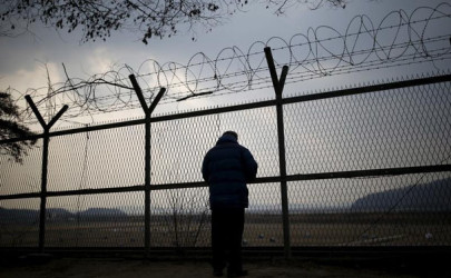A man looks through a barbed wire fence near the demilitarized zone separating the two Koreas in Paju, South Korea, February 8, 2015.  (Photo: Kim Hong-Ji / Reuters)