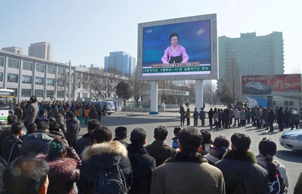 North Koreans watch a huge screen broadcasting an official announcement that the country