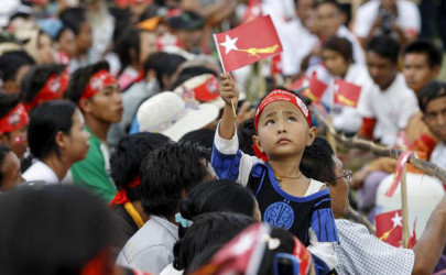 A boy waves a National League for Democracy (NLD) party flag during a speech by Aung San Suu Kyi in Loikaw, the capital of Karenni State, September 11, 2015. (Photo: Soe Zeya Tun / Reuters)