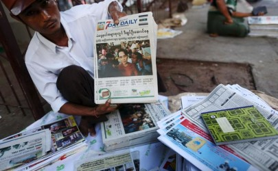 A news vendor displays local newspapers on a street in Yangon November 9, 2015. Voting unfolded smoothly in Myanmar on Sunday with no reports of violence to puncture a mood of jubilation marking the Southeast Asian nation's first free nationwide election in 25 years, its biggest stride yet in a journey to democracy from dictatorship.  REUTERS/Soe Zeya Tun