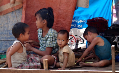 Children outside a makeshift shelter in a Hlaing Tharyar squatter settlement. (Photo: Moe Myint / The Irrawaddy)