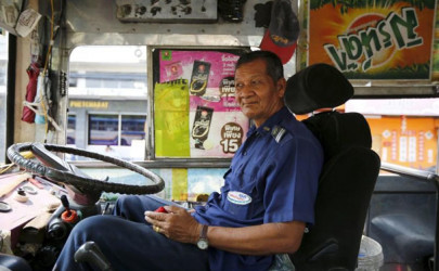 Plang Pansaior, a 66-year-old bus driver, waits for passengers while working in downtown Bangkok, Thailand, February 3, 2016.  (Photo: Jorge Silva / Reuters)