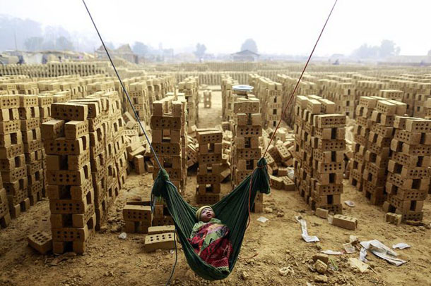 A boy sleeps in a hammock while his mother works at a brick kiln on the outskirts of Rangoon on February 1, 2015. (Photo: Soe Zeya Tun/ Reuters)