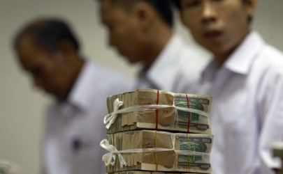 A stack of 1,000 kyat banknotes is seen as employees count money at Yoma Bank in Rangoon. (Photo: Reuters)