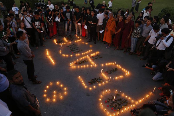 Buddhist monks and activists in Rangoon stand near lighted candles as they protest against a Burma Army artillery attack on a Kachin Independence Army (KIA) training center, on Nov. 24, 2014. (Photo: Soe Zeya Tun / Reuters)