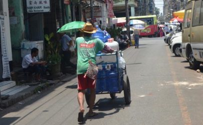 A man carts 20-liter bottles of water down a street in Rangoon. (Photo: Htet Khaung Linn / Myanmar Now)