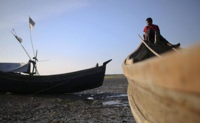 A Rohingya fisherman passes the time among boats at Thae Chaung IDP camp outside Sittwe on Nov. 13, 2014. (Photo: Minzayar / Reuters)