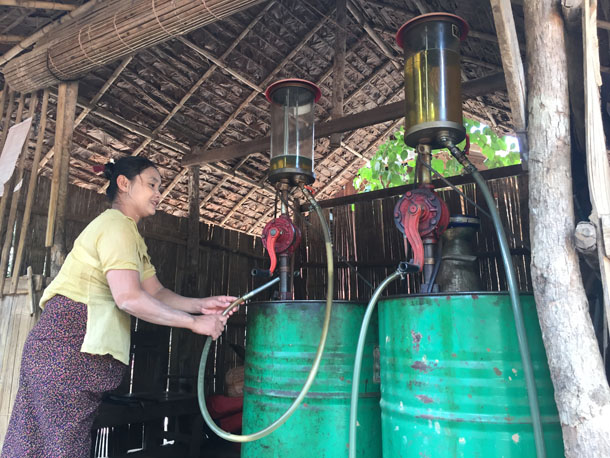 A purveyor of petrol fills canisters at a small station in Bilin Township, Mon State. (Photo: Saw Yan Naing / The Irrawaddy)