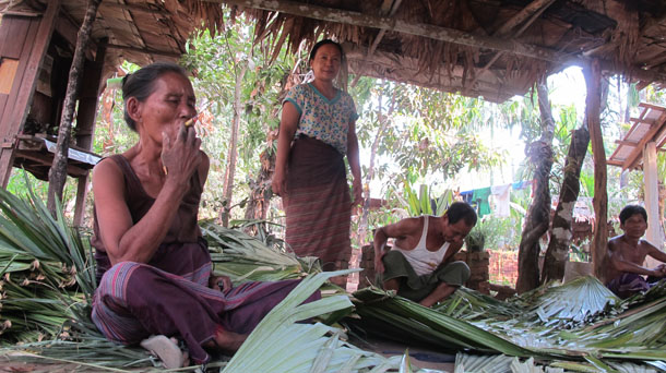Kyin Oo, a resident of Zee Won village, smokes a cheroot while talking to The Irrawaddy. (Photo: Saw Yan Naing / The Irrawaddy)