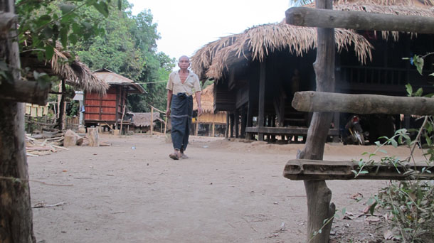 Maung Win, a former farmer who claims he was dispossessed of his land to make way for the rubber plantation, walks out of his home in Zee Won village. (Photo: Saw Yan Naing / The Irrawaddy)
