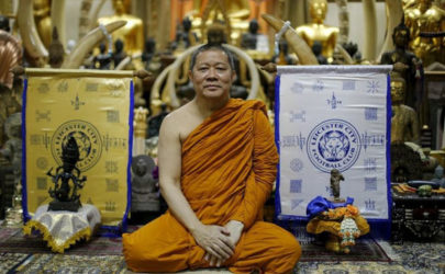 Buddhist monk Phra Prommangkalachan poses for a portrait next to holy cloths with Leicester City's logo on them, at his temple in Bangkok on April 18, 2016. (Photo: Reuters)