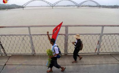 Nay Lin Soe, left, and his friend Kyaw Zin cross the bridge linking Mandalay and Sagaing on Monday. (Photo: Zaw Zaw / The Irrawaddy)