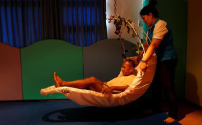 An elderly man receives help from a nurse during a physical therapy session at Bangkhae Home Foundation in Bangkok, Thailand, on April 27, 2016. (Photo: Reuters)