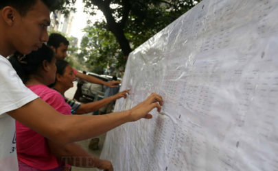 Rangoon residents check their names on a public display of voter lists in 2015. (Photo: J Paing / The Irrawaddy)