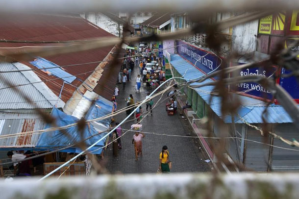 People are pictured through electric cables and wires at a street inside Bogyoke Aung San market in Rangoon on Nov. 6, 2013. (Photo: Minzayar / Reuters)