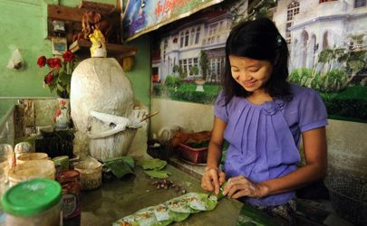 A seller rolls leaves containing betel nut at a stand in Rangoon. (Photo: Steve Tickner / The Irrawaddy)