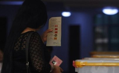 A woman holds a ballot slip and her national identity card before casting her vote at a polling station during by-elections in Rangoon on April 1, 2012. (Photo: Soe Zeya Tun / Reuters)