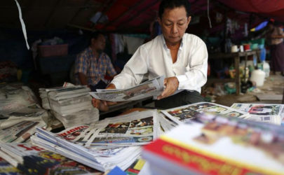 A man arranges newspapers at a wholesale market in Rangoon on Nov. 15, 2014. (Photo: Soe Zeya Tun / Reuters)