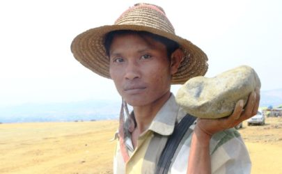 Maung Aye, a miner who has worked in Hpakant for many years, carries a piece of low-grade jade. (Photo: Htet Khaung Linn / Myanmar Now)