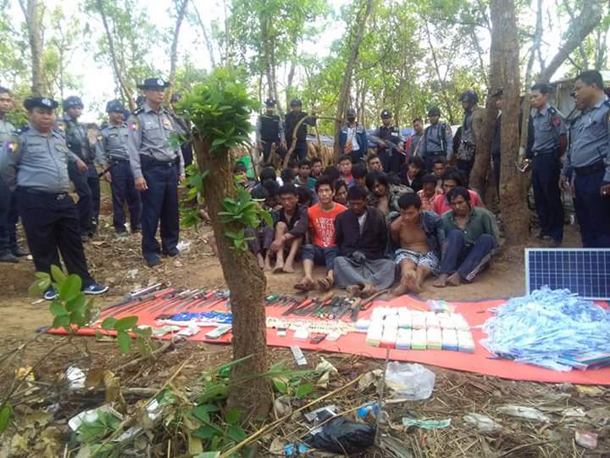 Alleged drug traffickers are seated in front of seized contraband in Lashio, Shan State. (Photo: Lashio News Diary / Facebook)