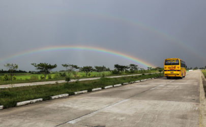 A rainbow is seen in the background as a bus plies the Rangoon-Mandalay highway. (Photo: The Irrawaddy)