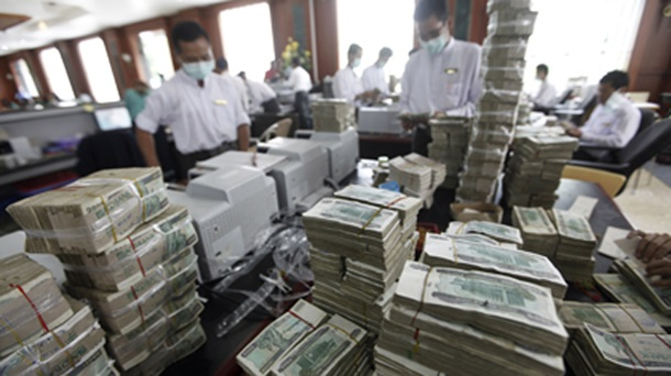 Cashiers behind piles of kyat banknotes in a private bank in Rangoon. (Photo: Reuters)