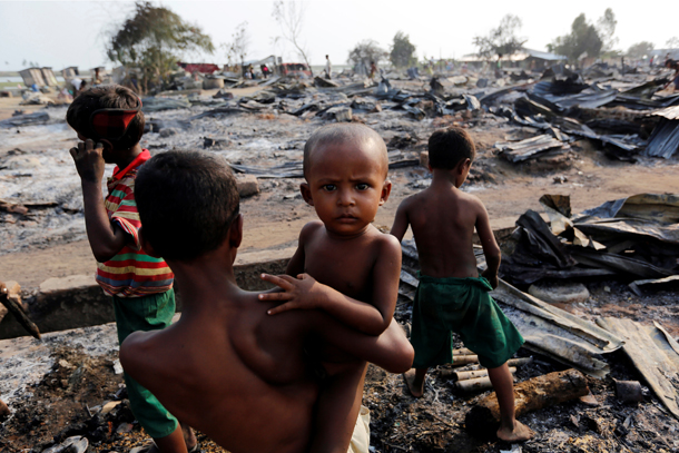 Boys stand among debris after fire destroyed shelters at a camp for internally displaced Rohingya Muslims in Arakan State on May 3, 2016. (Photo: Soe Zeya Tun / REUTERS)