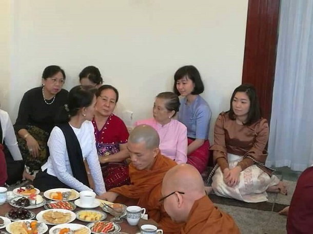 In this image from the commemorative events for Martyrs' Day on June 19 at 54 University Avenue, Daw Aung San Suu Kyi is seen turning to talk to Daw Khin Lay Thet, 6th from left, the wife of former general and USDP leader Shwe Mann. Daw Khin Lay Thet is seated in front of the couple's two daughters-in-law, Daw Zay Zin Latt, wife of Toe Naing Mann, and Daw Khin Hnin Thandar, wife of Aung Thet Mann. Also in the photo are, first left, Daw Khin Thet Htay, wife of First Vice-President Myint Swe, and, fourth left, Daw Cho Cho, wife of Speaker of Parliament Win Myint.