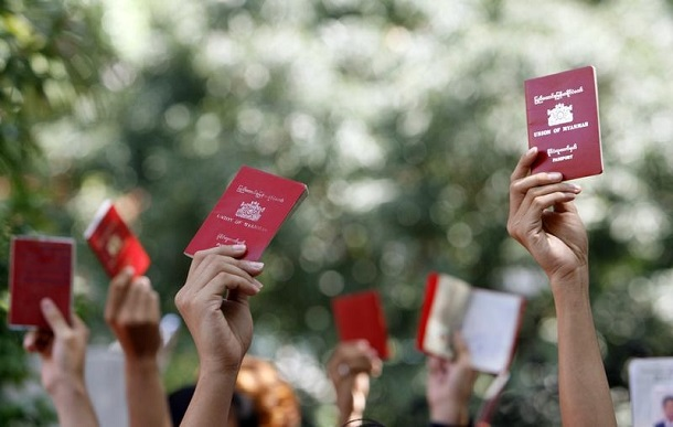 Myanmar nationals hold up their passports outside the Embassy of Myanmar in Singapore in 2008 as they waited for their turn to vote in the country's constitutional referendum. (Photo: Vivek Prakash / REUTERS)