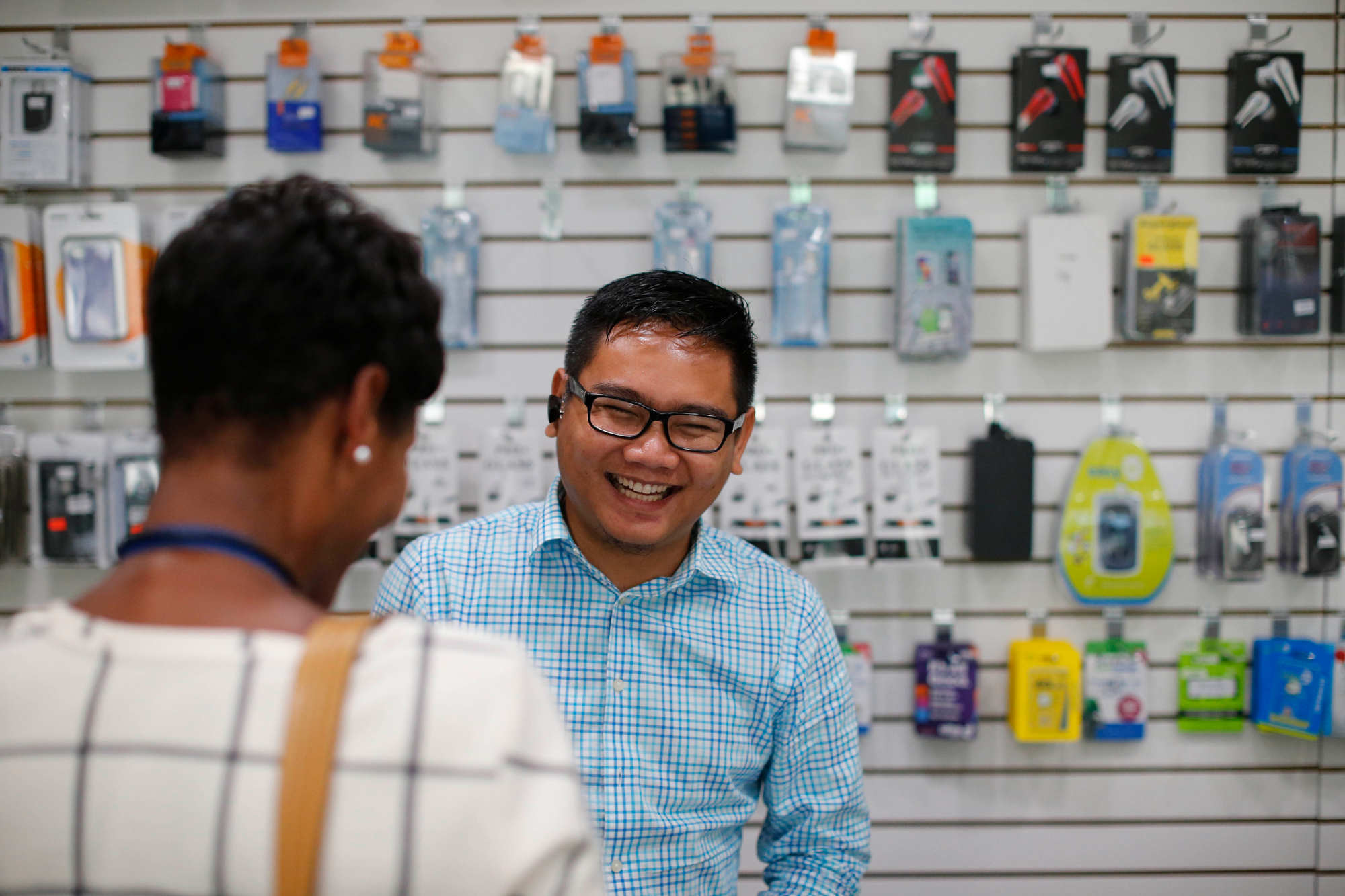 Aung Kaung Myat helps a customer at the counter of his iT Garden store on Grant Street, Sept. 20, 2016. (Derek Gee/Buffalo News)