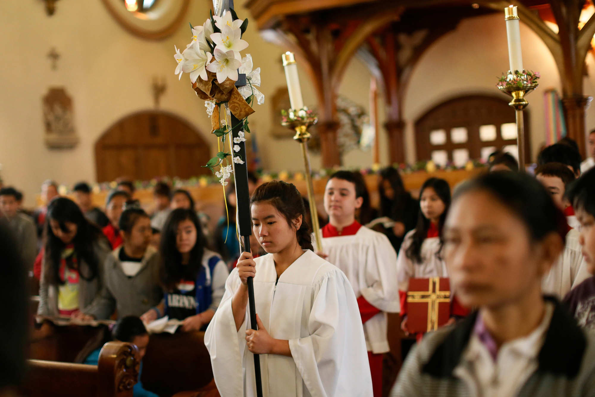 Beh Meh carries the cross to lead the processional at the start of Mass at Our Lady of Hope, April 19, 2015. (Derek Gee/Buffalo News)