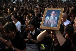 Mourners pray as a woman holds up a portrait of Thailan…