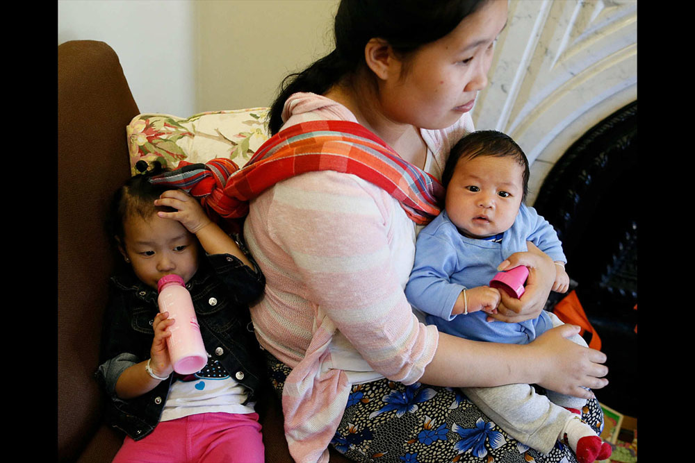 Bu Meh, a Karenni refugee from Burma, has her daughter, Cecilia Meh, 2, and 2-month-old son Nathan David in tow during an open session with a Burmese-speaking doula at The Priscilla Project, a program to help pregnant women and new mothers through childbirth and parenting as new Americans, June 11, 2015. (Derek Gee / Buffalo News)