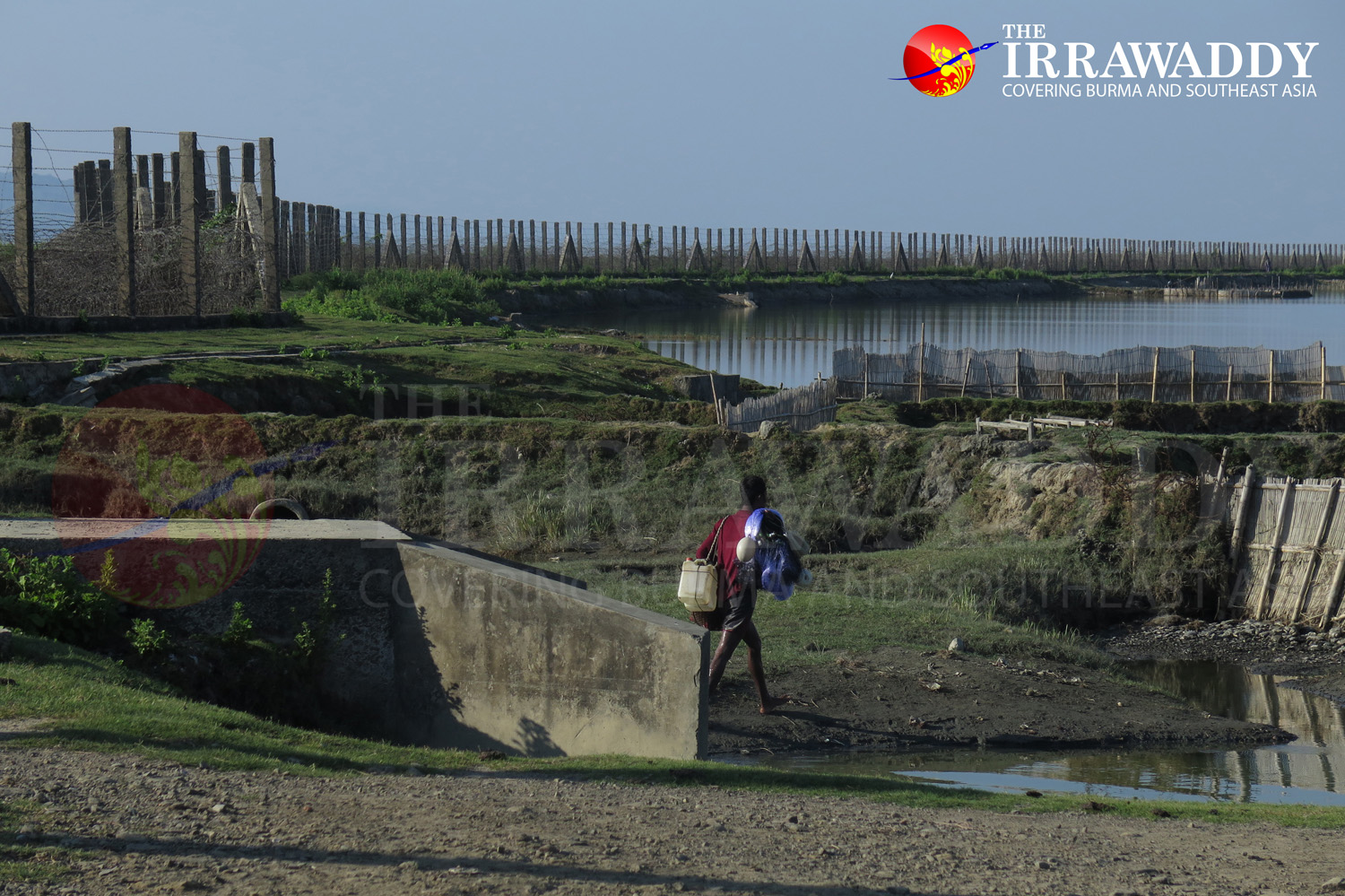 A fisherman walks near the border fence in the western part of Maungdaw town. (Photo: Moe Myint / The Irrawaddy)