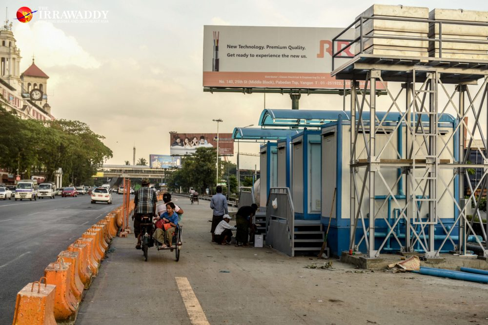 Workers prepare public toilets at one of the designated vendor locations on Strand Road. (Photo: Pyay Kyaw / The Irrawaddy)